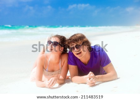 romantic couple lying on white sand at tropical beach - stock photo