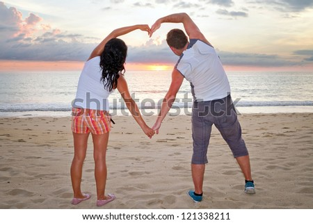 Romantic couple making heart shape with arms at sunset - stock photo