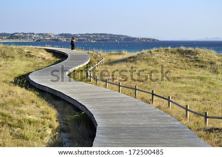 Romantic couple. Man and woman in a wooden pathway enjoy the landscape - stock photo