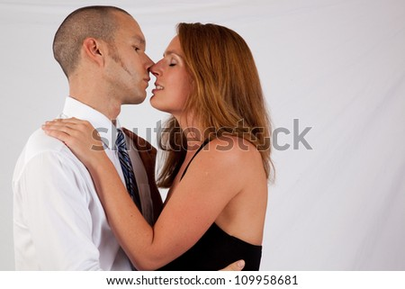 Romantic couple, man and woman, standing in an embrace and close to a kiss