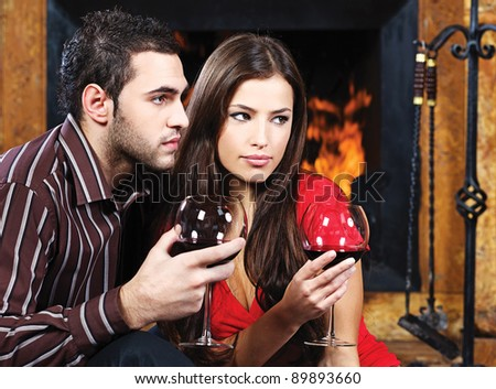 Romantic couple near fireplace drinking red wine - stock photo