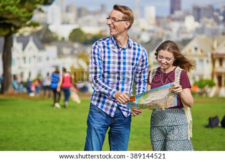 Romantic couple of tourists using map and planning their itinerary in San Francisco, California, USA