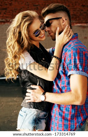 Romantic couple of young people in love posing outdoors over city background. - stock photo