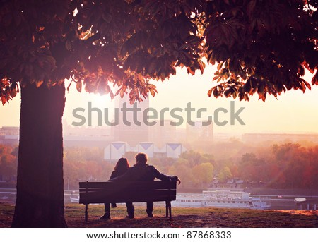 Romantic Couple on a Bench by the River - stock photo