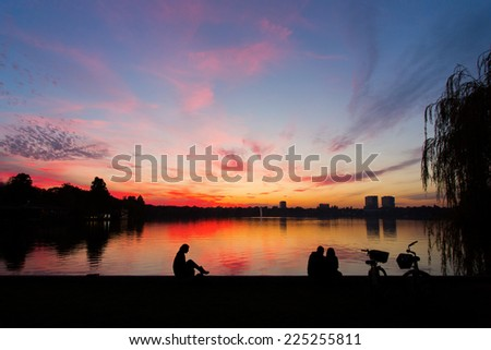 Romantic couple on a lake at sunset with bike - stock photo
