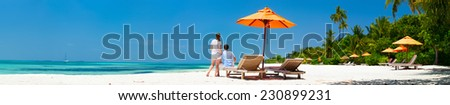 Romantic couple on a tropical beach during honeymoon vacation, wide panorama perfect for banners - stock photo