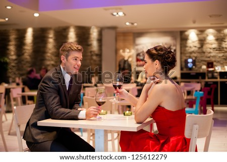 Romantic couple on dating in restaurant, smiling and enjoying - stock photo