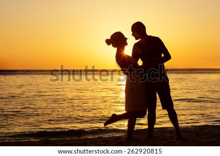 Romantic couple on the beach at colorful sunset on background - stock photo