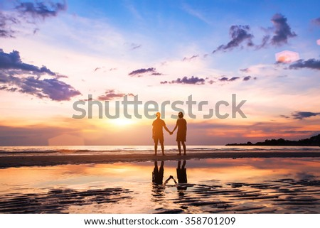 romantic couple on the beach at sunset, silhouettes of man and woman together