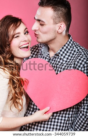 Romantic couple on valentines day. Happy joyful man and blinking woman holding heart symbol. Love concept.