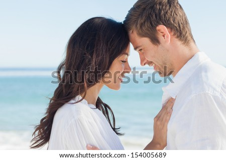 Romantic couple relaxing and embracing on the beach during the summer - stock photo