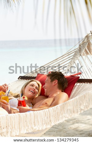 Romantic Couple Relaxing In Beach Hammock - stock photo