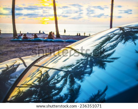 Romantic couple relaxing in tropical beach lounge at yellow sunset sky with clouds background Many a lot teenager people talking drinking and resting on evening romantic coast Reflection on car glass  - stock photo