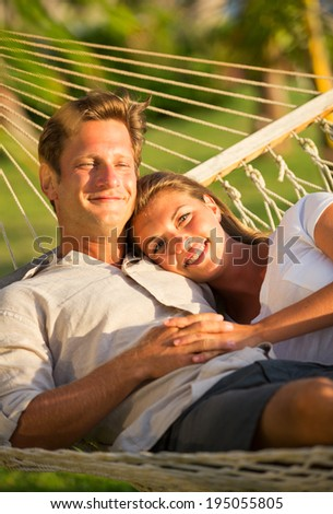 Romantic couple relaxing in tropical hammock at sunset - stock photo