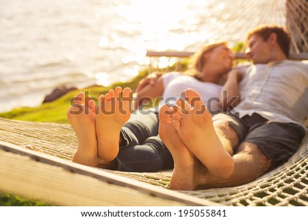 Romantic couple relaxing in tropical hammock at sunset, Shallow depth of field, focus on feet. - stock photo