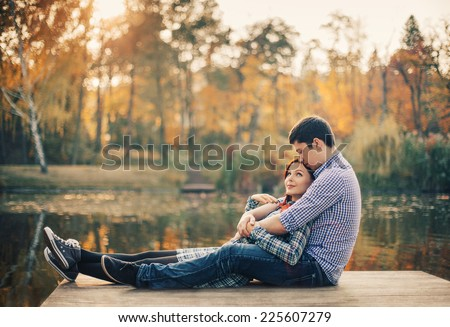 Romantic couple relaxing on the river dock in autumn park - stock photo