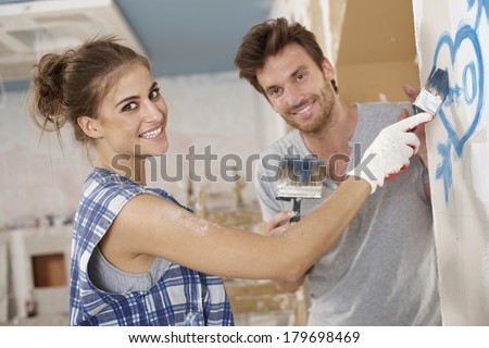 Romantic couple renovating house, painting heart on wall, smiling happy. - stock photo