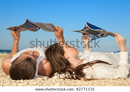 Romantic couple resting on beach and reading magazines - stock photo