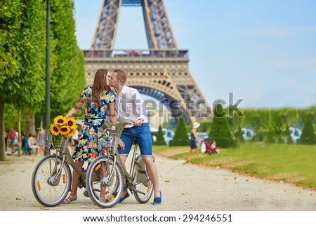 Romantic couple riding bicycles near the Eiffel tower in Paris - stock photo