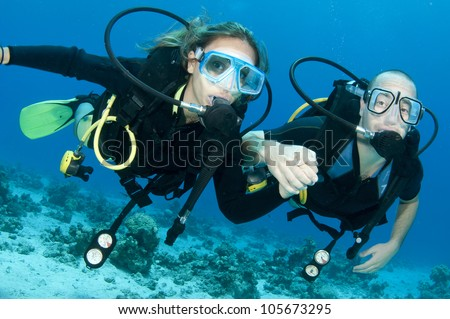 romantic couple scuba dive together in the ocean on a coral reef - stock photo