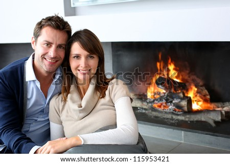 Romantic couple sitting by fireplace at home - stock photo
