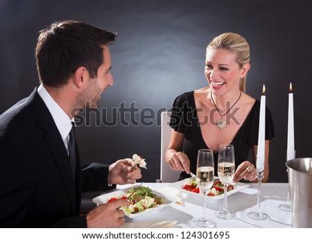 Romantic couple sitting having dinner in an elegant restaurant - stock photo