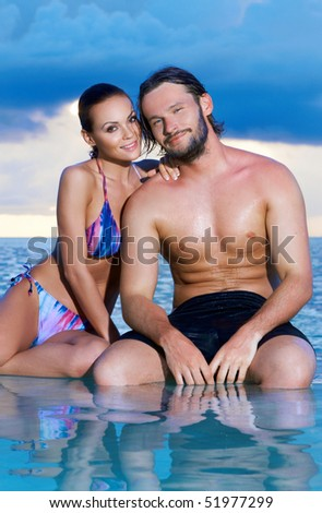 Romantic couple sitting next to swimming pool