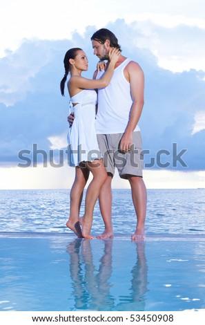 Romantic couple sitting next to swimming pool - stock photo