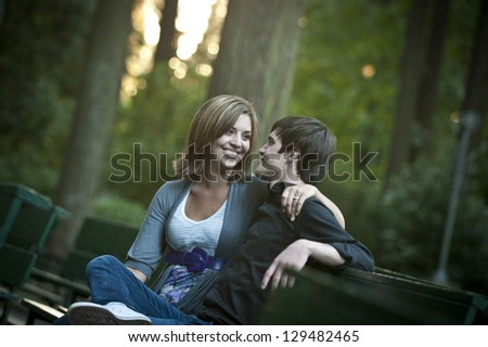 Romantic couple sitting on a bench - stock photo