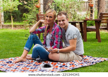 Romantic couple sitting on a blanket with tablet pc and mobile phone at summer green park. They are happy.