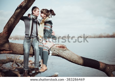 Romantic couple sitting on a branch near the water.