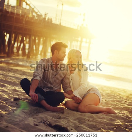 romantic couple sitting on beach with golden sunset by beach - stock photo