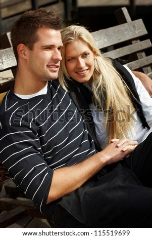 Romantic couple sitting on bench, hugging, smiling, enjoying autumn sun. - stock photo
