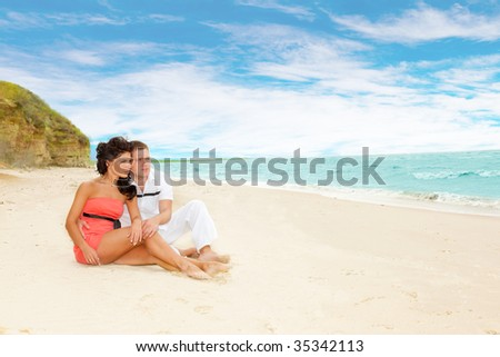 Romantic couple sitting on sand and looking at the sea - stock photo