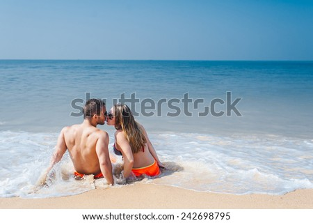 Romantic couple sitting on the beach and enjoying beautiful sea view