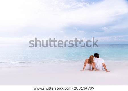 Romantic couple sitting on the beach and enjoying beautiful sea view, side view, spending time together, summer vacation concept