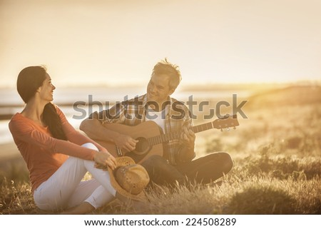 Romantic couple sitting on the beach at sunset with the man playing the guitar - stock photo