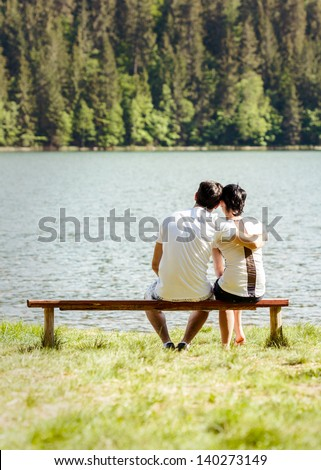 Romantic couple sitting on wooden bench near big lake