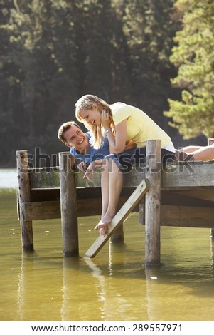 Romantic Couple Sitting On Wooden Jetty Looking Out Over Lake - stock photo
