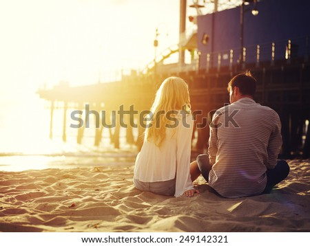 romantic couple sitting together by the beach with sunset - stock photo