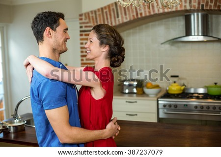Romantic couple standing face to face and embracing each other in kitchen - stock photo