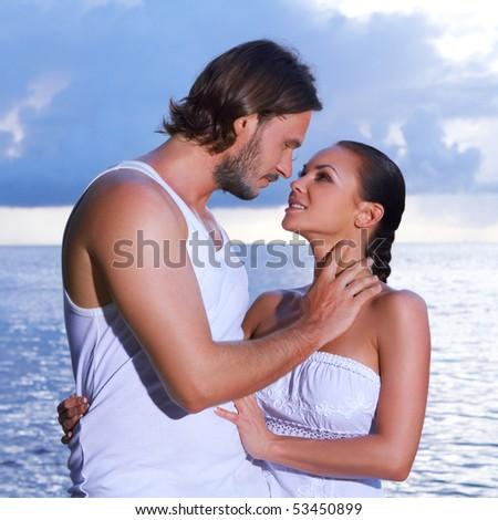 Romantic couple standing next to palm tree - stock photo