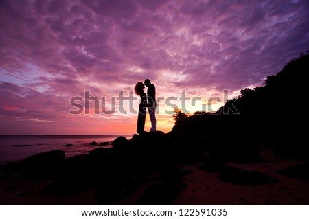 romantic couple standing on rocks by sea on purple dramatic sunset background - stock photo