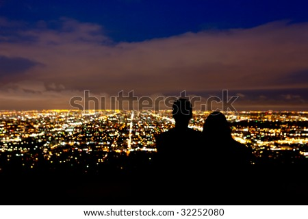 Romantic couple takes in the view the city lights - stock photo