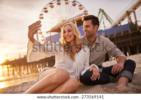 romantic couple taking selfie at sonica monica laying in sand - stock photo
