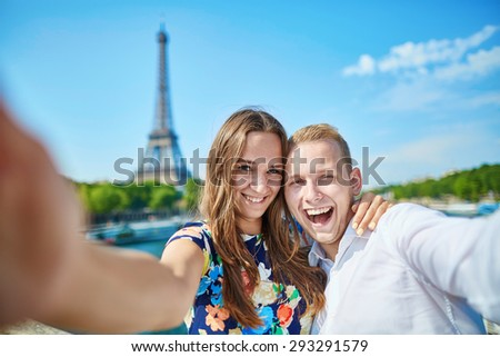Romantic couple taking selfie with mobile phone near the Eiffel tower in Paris - stock photo