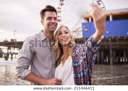 romantic couple taking selfies together in santa monica - stock photo