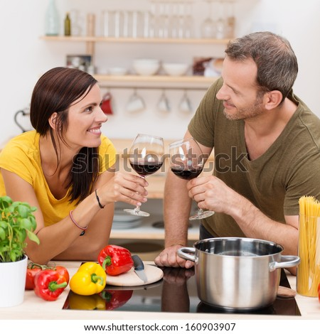 Romantic couple toasting each other in the kitchen with glasses of red wine as they prepare a healthy meal of spaghetti and vegetables together