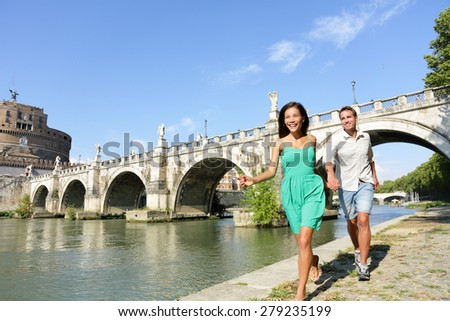 Romantic couple tourists walking Castel Sant Angelo, Rome. Happy romantic couple looking at the roman castle enjoying their romantic summer holiday travel in Italy, Europe. Man and woman holding hands - stock photo