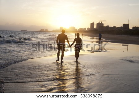 Romantic couple walking along the beach at sunset.